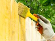 Eine Frau streicht eine Holzterrasse mit Holzöl. Der Vorher-nachher-Effekt ist eindeutig zu erkennen.